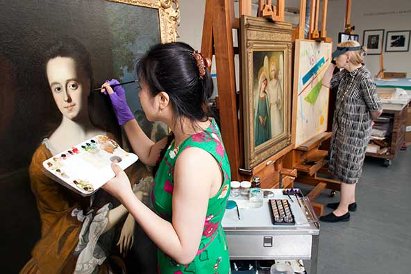 Andrew W. Mellon Fellow in Paintings Conservation Hae Min Park treating an 18th c. painting
