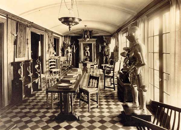 A room in Higgins' home with table, chairs and a variety of objects from his collection on display, including suits of armor and weapons