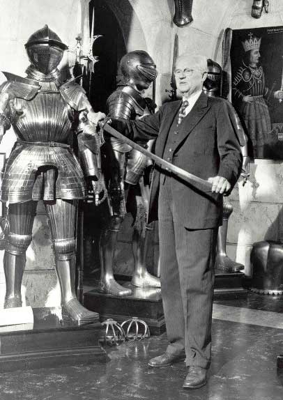 John Woodman Higgins wearing a suit and holding a sword, surrounded by objects from his collection
