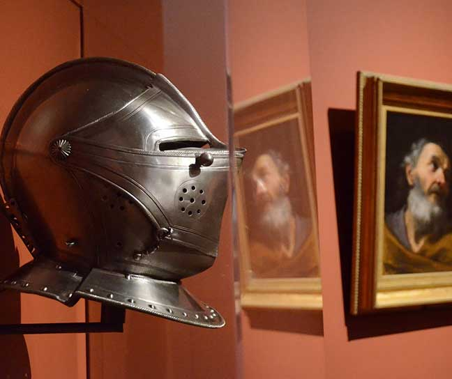 A knight's helmet on display in a [remastered] painting gallery at WAM