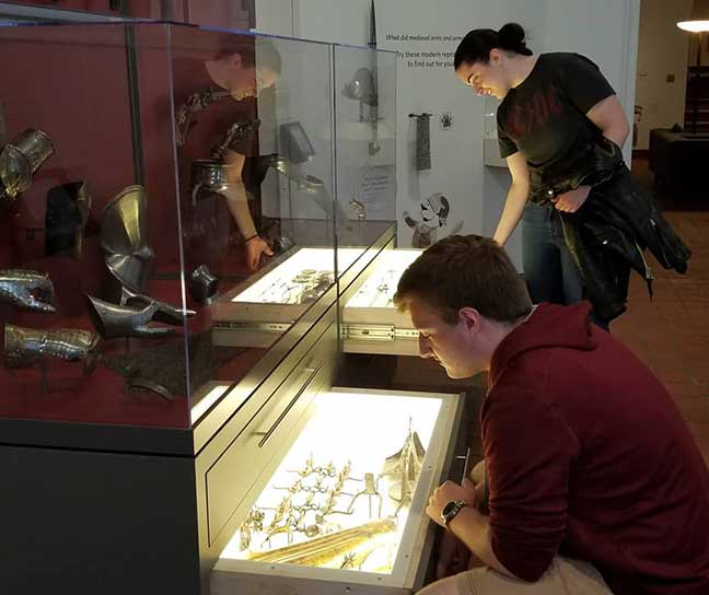 Museum visitors viewing Higgins Armory Collection objects in open storage