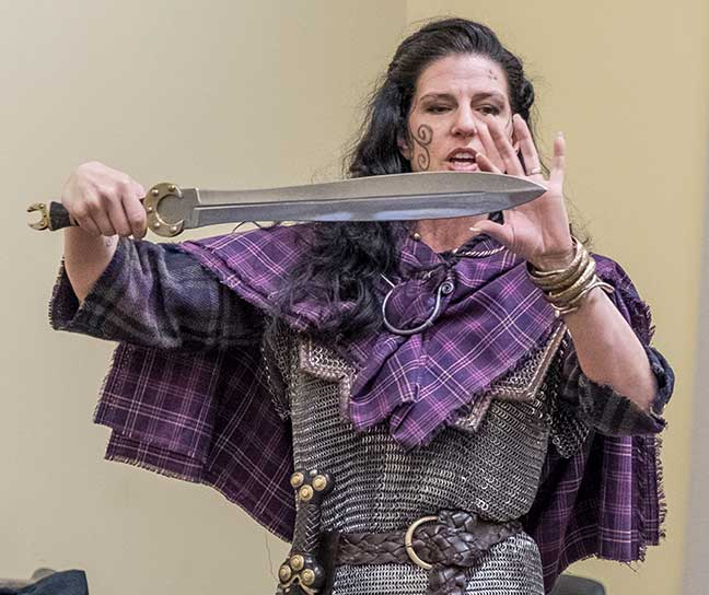 A female costumed interpreter wearing chainmail and brandishing a sword