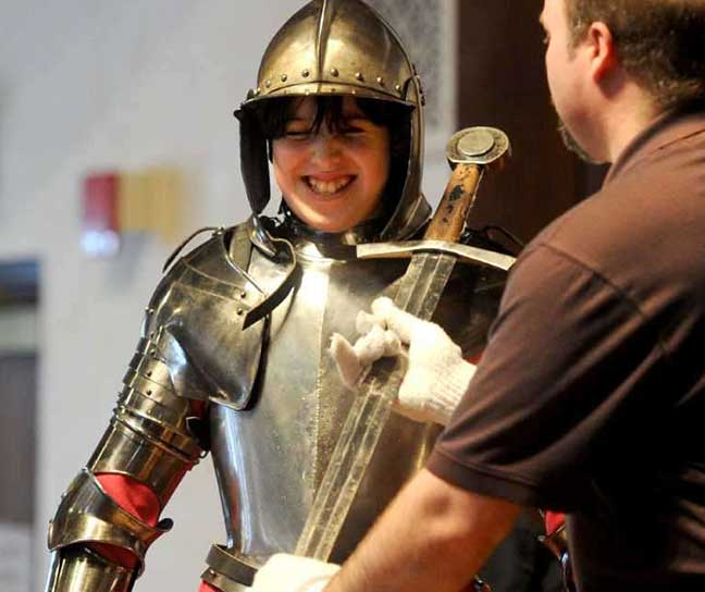 A laughing boy, dressed up in real armor, is offered a sword by an educator