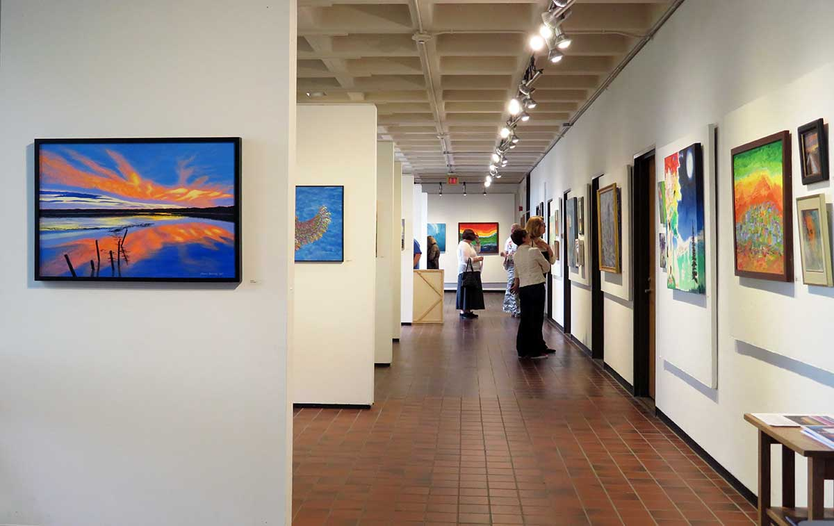View of the Higgins Education Wing 1st floor walkway with adult student artwork on display
