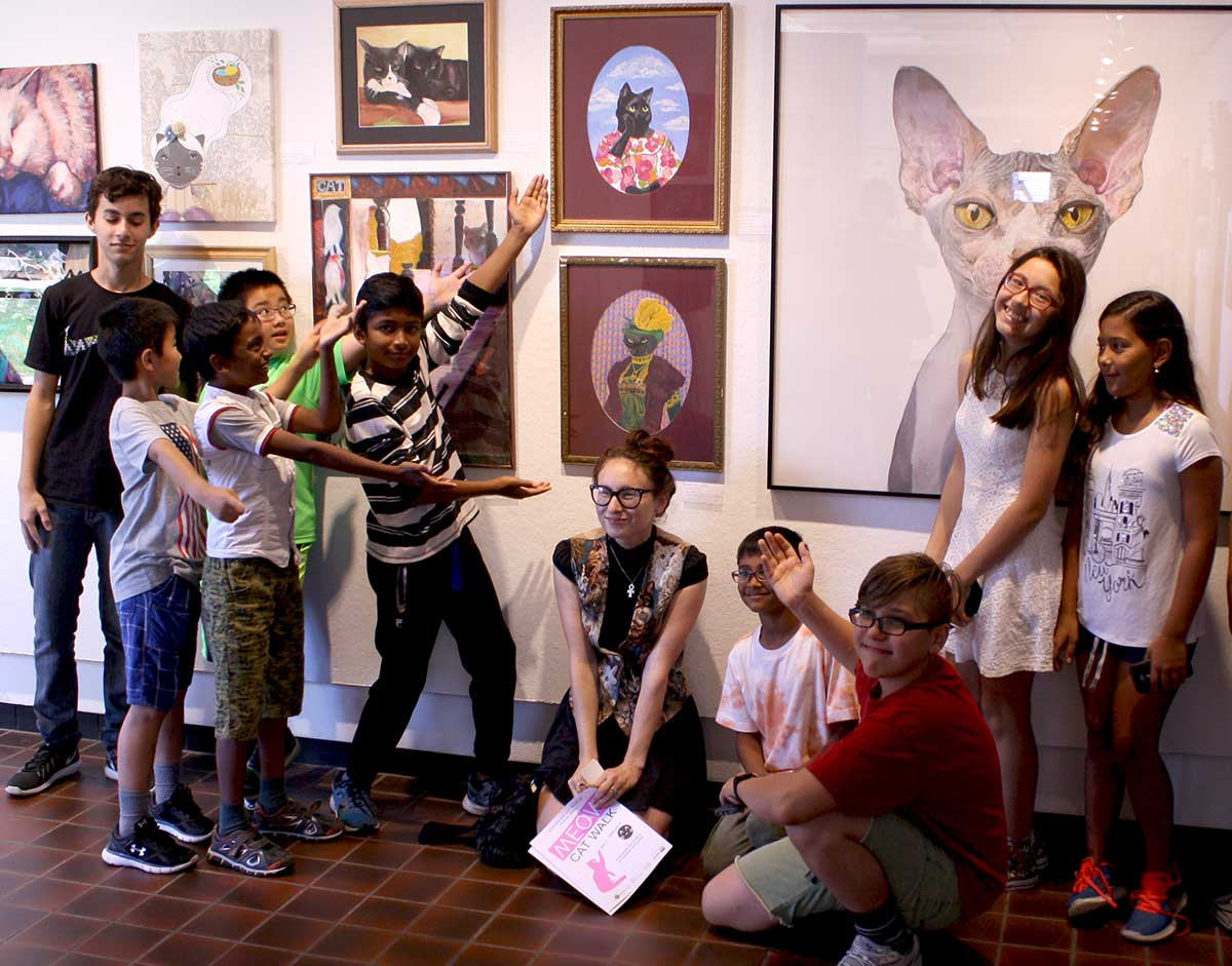 Young artists enthusiastically present their artwork to the photographer