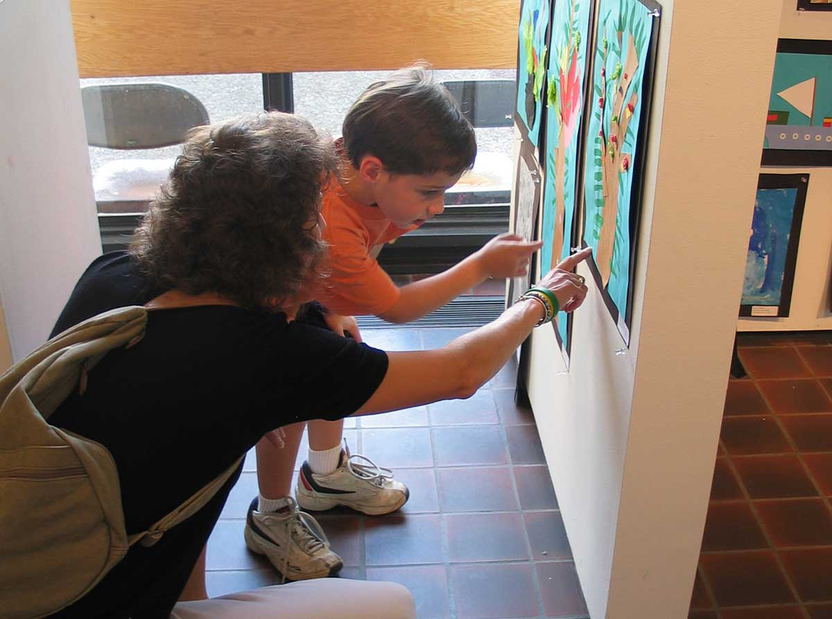 A small boy and his mother crouch down to examine (his?) artwork on during a Youth CLasses exhibition opening