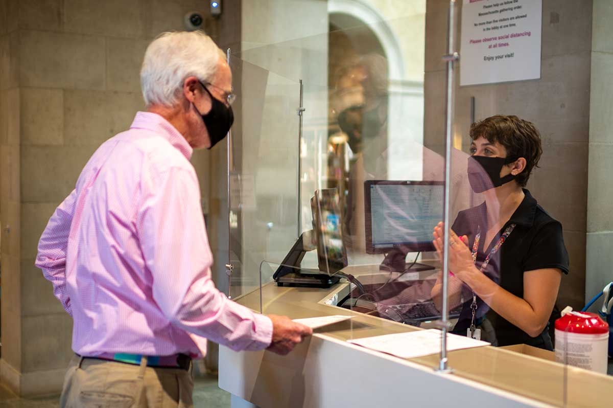 A guest services staff member attends to a Museum visitor