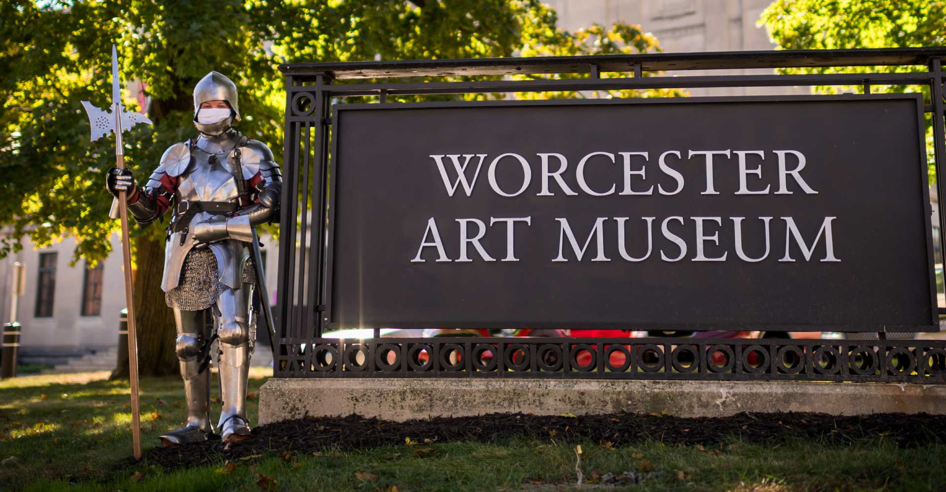 Programming Coordinator Neal Bourbeau, dressed in full medieval armor and wielding a pike, stands beside a WAM sign in the Museum grounds